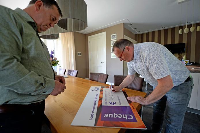 Uitbater Aloys Nijhuis van horecabedrijf Fraans Marie in Albergen (rechts)  vult een cheque in voor de Samenloop voor Hoop Tubbergen. Links voorzitter Henny Oude Geerdink van de Samenloop voor Hoop Tubbergen.