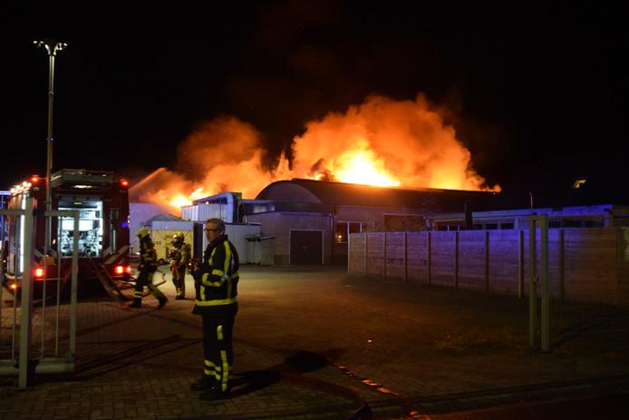 De vlammen slaan uit het dak van de kozijnenfabriek in Zelhem.
