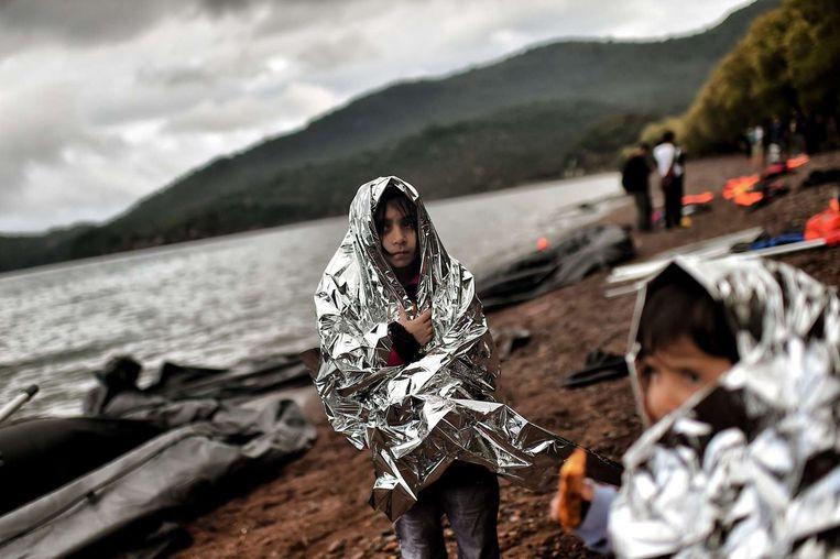 Enkele kinderen zijn pas aangekomen op het Griekse strand van Lesbos. Beeld afp
