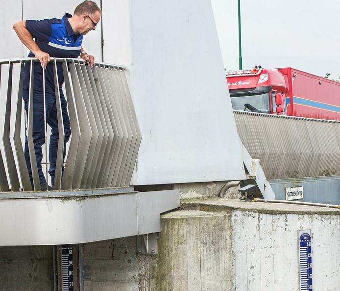 Havenmeester Jan van den Berg controleert de waterhoogte bij de Macharense brug.