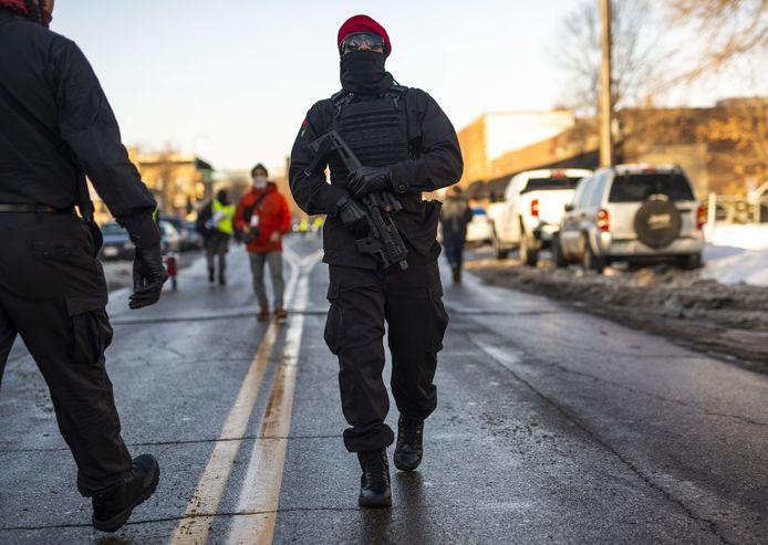 Een gewapende activist van de New Black Panther Party patrouilleert bij de demonstratie.