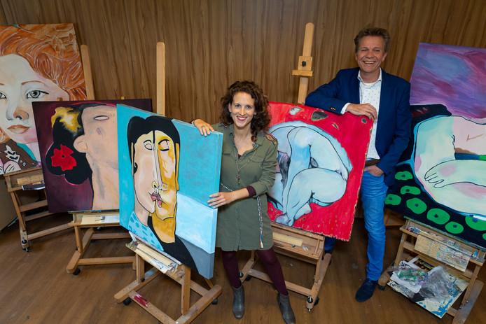 Portret van Sjef Enthoven en Renate Volkers tussen de kunstwerken die gemaakt zijn door Korsakovpatienten.
