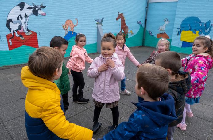 Kleuters vieren in een kringetje dat er een prachtige muurschildering op de schoolmuren van De Lichtboei staat. Hailey, vier jaar, staat in het midden, zij vindt 'alle dieren even mooi'.