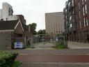 De locatie waar de nieuwbouw gaat verrijzen, met rechts de appartementen van Twee!
