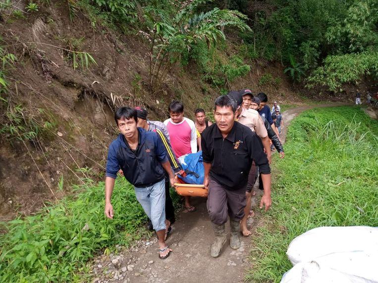 Reddingswerkers dragen het lichaam van een slachtoffer. Beeld Reuters