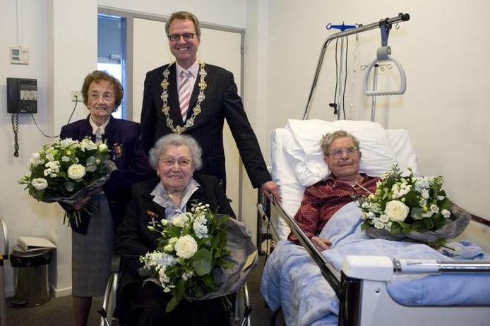 In ziekenhuis Lievensberg kregen Mientje Houtman, Corry van de Boom en Piet Huijgens (vlnr) de NU-speld van burgemeester Polman. foto Tonny Presser/het fotoburo