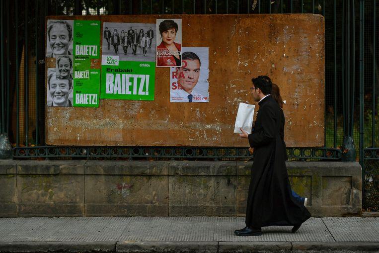 Een Spaanse priester loopt langs een muur met verkiezingsposters in het Noord-Spaanse Tafalla. Afgelopen zondag waren de vierde verkiezingen in vier jaar.  Beeld AP