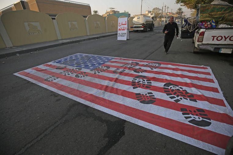 Een Amerikaanse vlag is in Bagdad op straat geschilderd zodat auto's eroverheen kunnen rijden. Westerse regeringen vrezen voor represailles na de dood van de Iraanse generaal Soleimani.  Beeld AFP