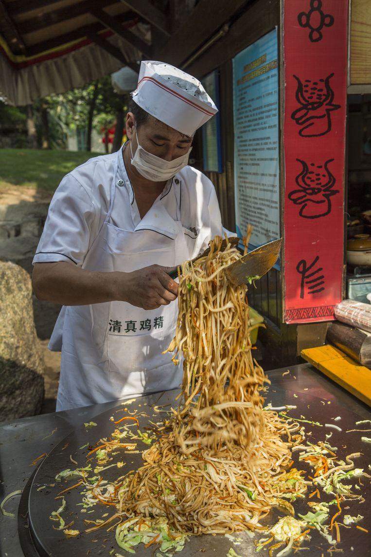 Een kok bereidt eten bij een marktkraam in Splendid China Park, Shenzhen. Beeld null