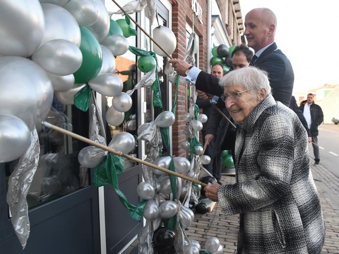 Bè Boone en burgemeester Rob van der Zwaag openen Bij Boone door tientallen ballonnen door te prikken.