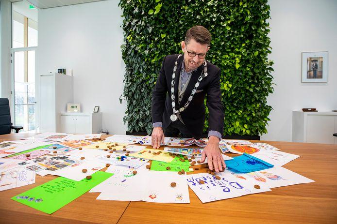 Burgemeester Bouke Arends met de tekeningen die kinderen gemaakt hebben voor Sinterklaas.