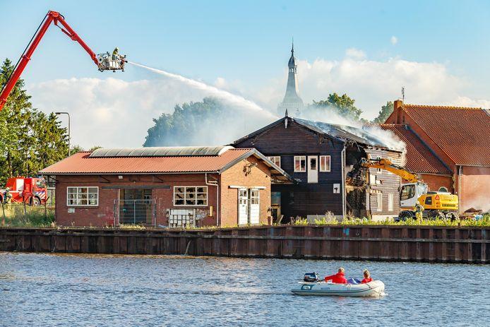 Uit voorzorg wordt het oude houten kantoorpand waar de brand woedde gesloopt. Boven het pand steekt de spits van de kerktoren van de Grote Kerk in Hasselt uit. Brand bij voormalig scheepswerf Bodewes.