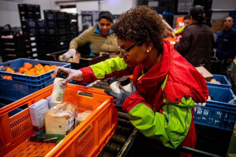 Een vrijwilliger van de Voedselbank pakt een pakket in.  Beeld ANP
