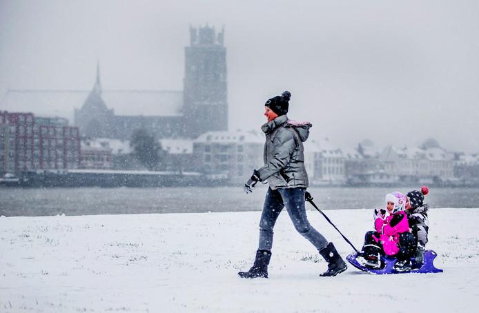 Het plezier spat er vanaf bij deze kinderen in Zwijndrecht. Terwijl de sneeuwvlokken op hen neer vallen, worden ze op hun sleetje langs de oevers van de Oude Maas voortgetrokken.