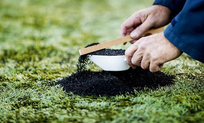 Een onderzoeker schept rubberkorrels van een kunstgrasveld.