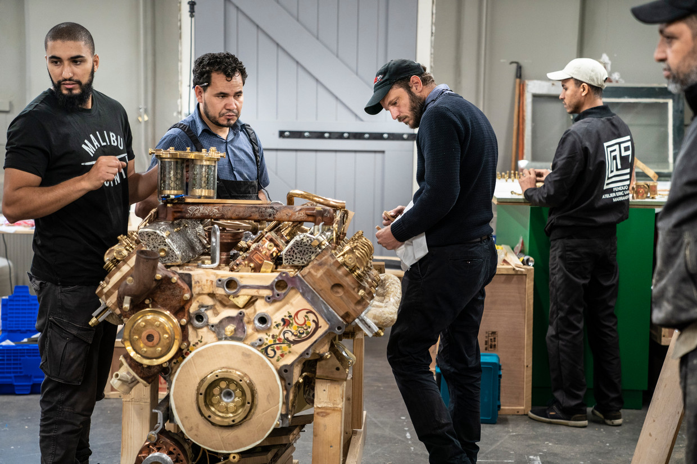 Éric Van Hove (naast de motor, met donkere pet) maakt met ambachtslieden in het Fries Museum de motor van een veldhakselaar na.