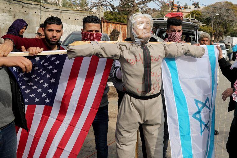 Palestijnen demonstreren tegen de vredesplannen van president Trump. De vlaggen en beeltenis van Trump steken zij in brand. Beeld Reuters