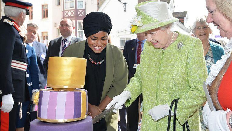 Queen Elizabeth snijdt de taart aan die winnares van The Great British Bake Off, de Britse variant van Heel Holland Bakt, Nadiya Hussain voor haar 90ste verjaardag bakte. Beeld Reuters