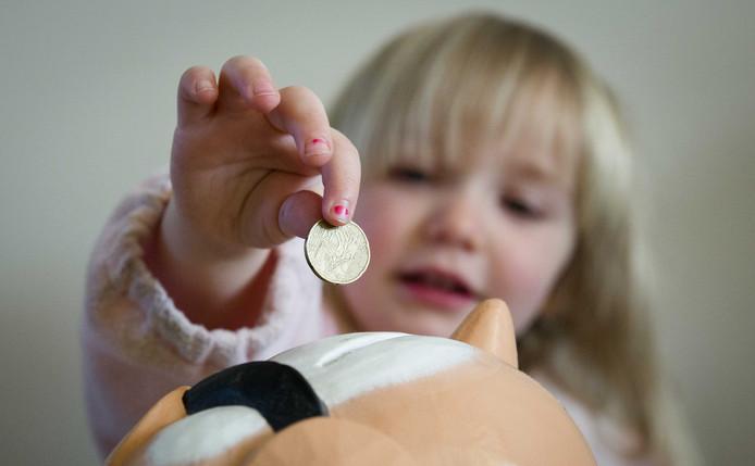 Een meisje stopt geld in haar spaarpot. Het verdwijnen van munten en briefjes maakt het voor kinderen moeilijker de waarde van geld in te zien.