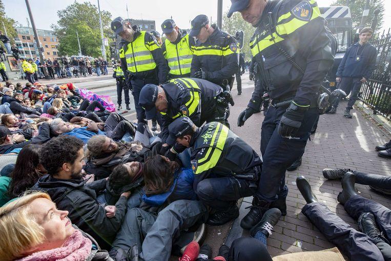 Activisten van Extinction Rebellion worden aangehouden bij een blokkade vorig jaar op de Stadhouderskade. Beeld ANP