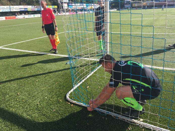 Berkum speler Robert Schonewille repareert eigenhandig een gat in het net achter keeper Huib Veurink. Het duel tegen Urk eindigde in 1-1.