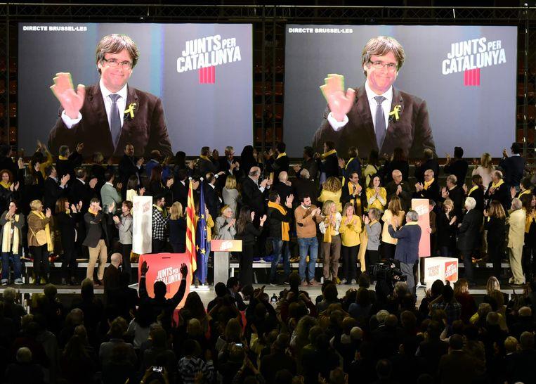 Carles Puigdemont wuift vanaf een scherm naar zijn aanhang in Catalonië. Beeld afp