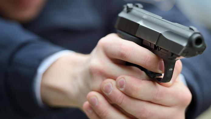 Een agent met getrokken pistool.