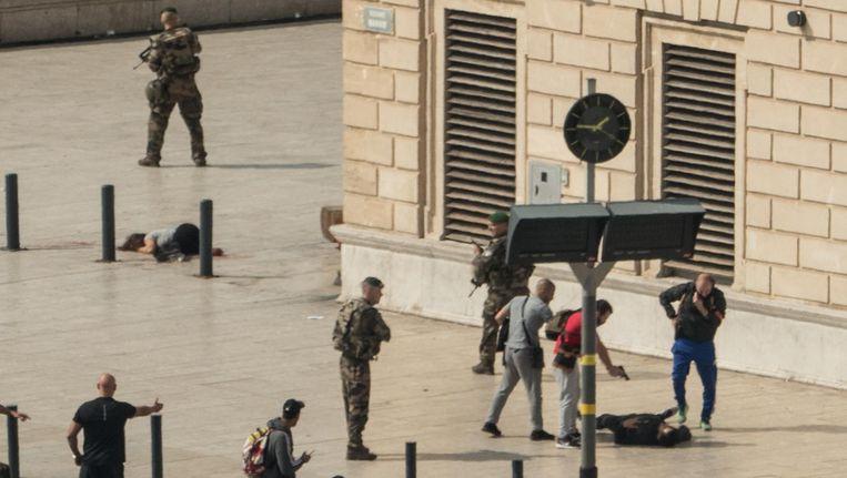 Een Franse agent richt zijn pistool op de dader van de steekpartij in Marseille. Links ligt een van de slachtoffers op de grond. Beeld AFP
