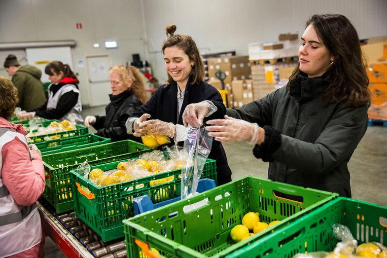 Bij de voedselbank in Rotterdam worden voedselpakketten samengesteld door vrijwilligers. Studenten of mensen die tijdelijk geen werk hebben vanwege de corona crisis hebben zich gemeld bij 'ready to help' van het Rode Kruis of rechtstreeks bij de voedselbank. Beeld Arie Kievit