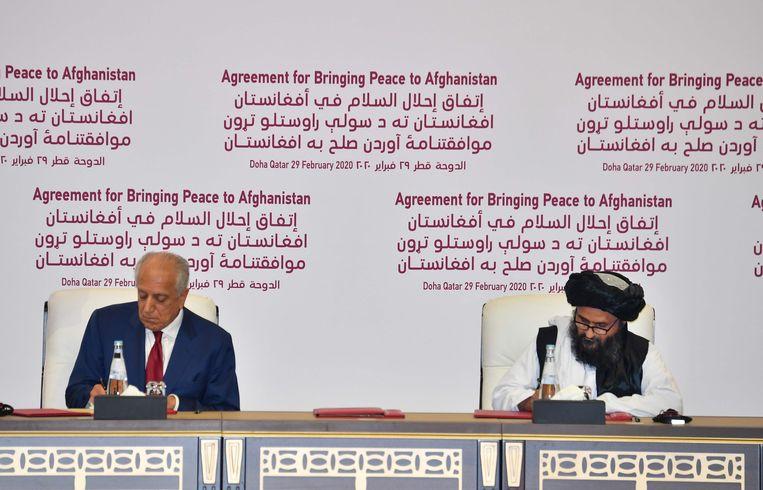 De Amerikaanse 'speciale afgezant voor de verzoening in Afghanistan' Zalmay Khalilzad (links) en Taliban mede-oprichter Mullah Abdul Ghani Baradar zaterdag in Doha bij de ondertekening van het vredesakkoord tussen de VS en de Taliban. Beeld AFP