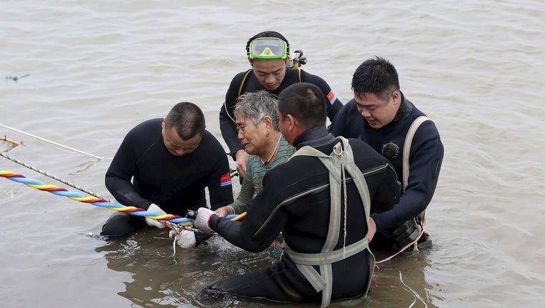 Een overlevende wordt door reddingswerkers uit het water geholpen. Beeld Reuters