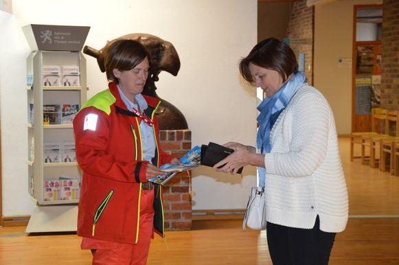 Vrijwilligers van het Rode Kruis delen de eerste stickers uit aan de gemeenteraadsleden voor aanvang van de gemeenteraad.