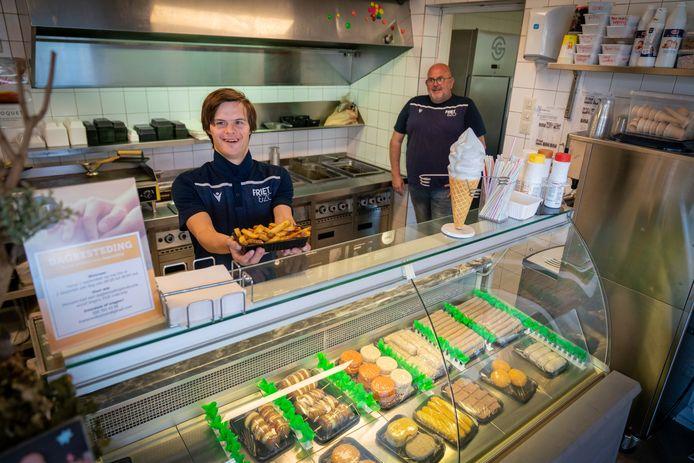 Bob van Gerven is klaar om een klant zijn frietje te brengen. Anthony Uffing kijkt goedkeurend toe.
