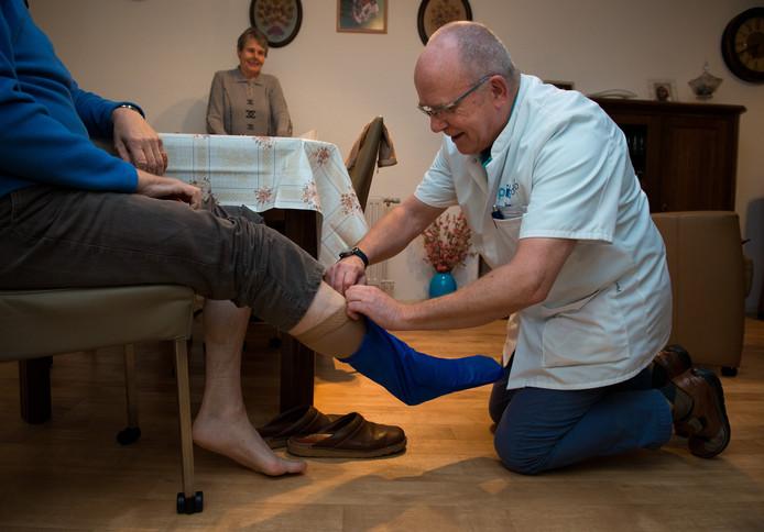 Een verpleger helpt een patiënt met het aantrekken van steunkousen in een aanleunwoning.