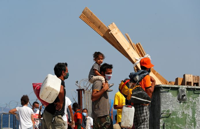 Vluchtelingen en migranten van het verwoeste kamp Moria stonden vorige week in de rij om een nieuw tijdelijk kamp te betrekken.