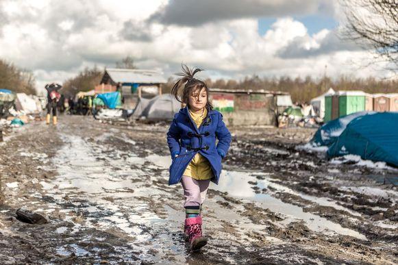 Een meisje wandelt door de modder in het vluchtelingenkamp in Duinkerke, in maart dit jaar.