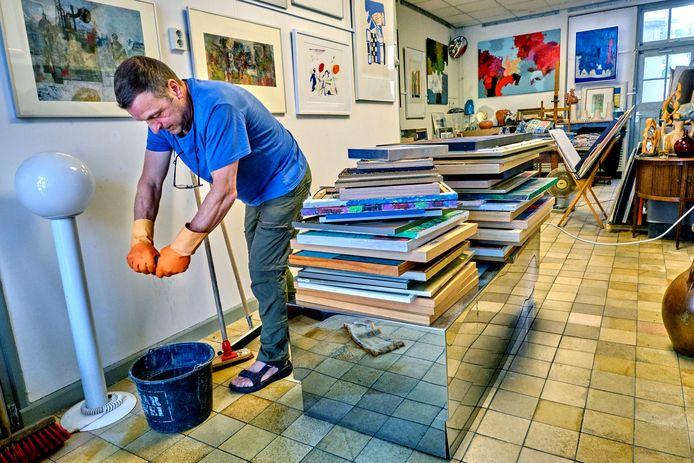 Werner Nemes wringt een dweil uit, door een wolkbreuk  kwam zijn hele kunstwinkel in de Nieuwstraat onder water te staan.