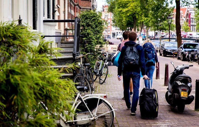Toeristen met rolkoffers op de Amsterdamse grachten. Beeld anp