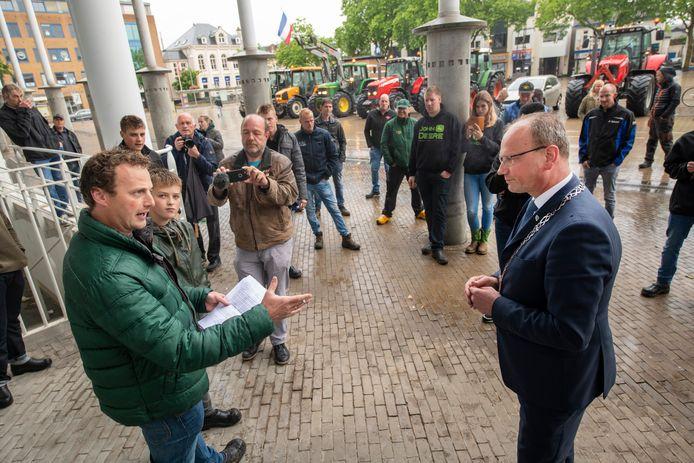 Burgemeester Heerts neemt een brief van de boeren in ontvangst, met het verzoek die te laten voorlezen voordat de gemeenteraad over hun onderwerp praat.