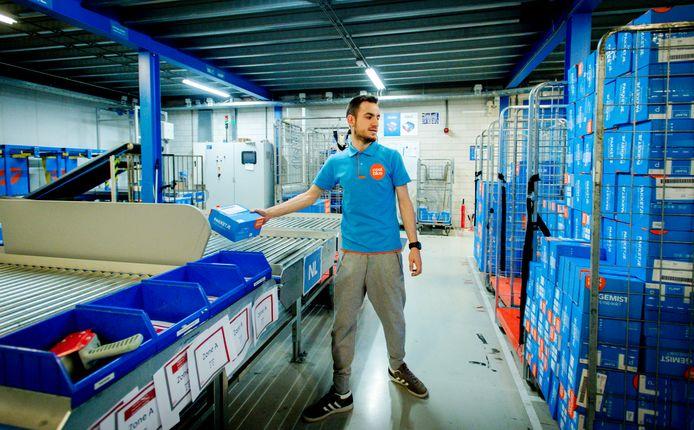 Een medewerker van Coolblue verwerkt pakketjes in het magazijn van de online retailer.