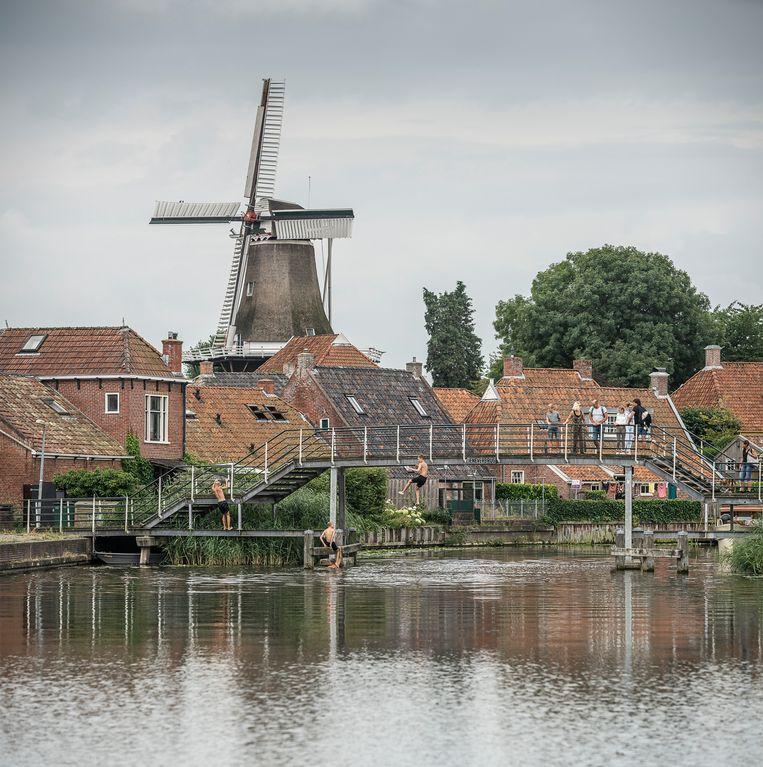 Zicht op Winsum met het Winsumerdiep en molen de Vriendschap, op de voorgrond de jeneverbrug.  Beeld Harry Cock