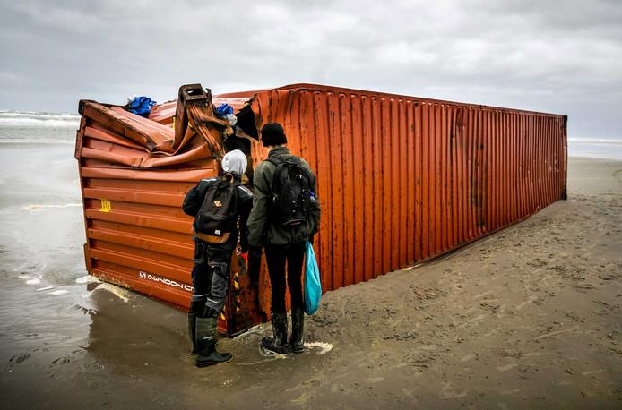 Vrijwilligers helpen bij het opruimen van de aangespoelde containers en spullen