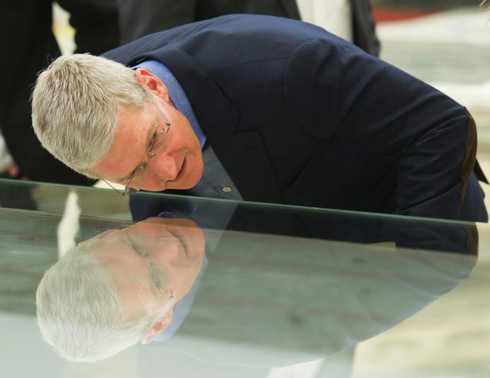 Topman Tim Cook van Apple inspecteert een van de glazen panelen die gebruikt werden in het hoofdkantoor.
