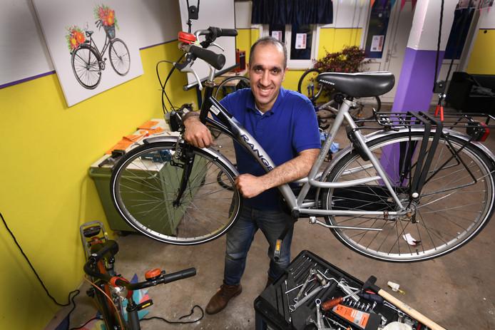 Hamidreza Zerangi neemt een fiets onder handen in de fietsenwerkplaats op het AZC in Leersum.