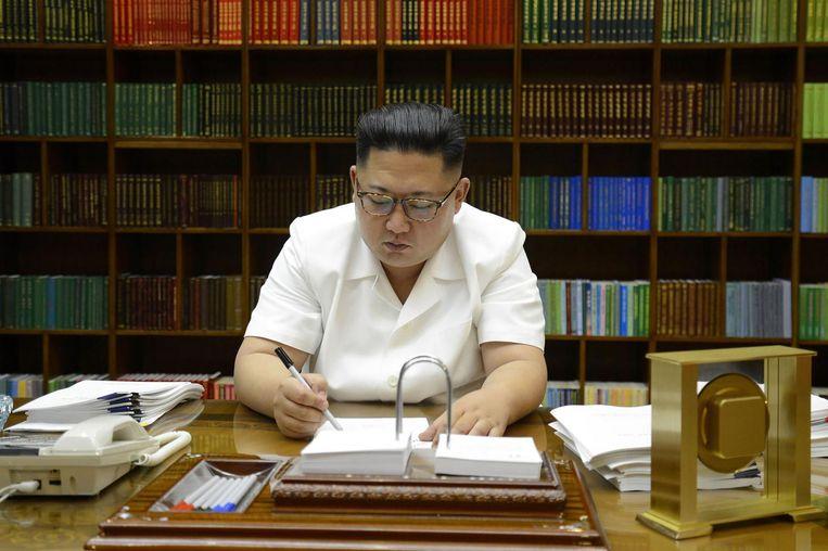 De Noord-Koreaanse leider Kim Jong-Un tekent documenten voor de testlancering van een intercontinentale raket. Beeld afp