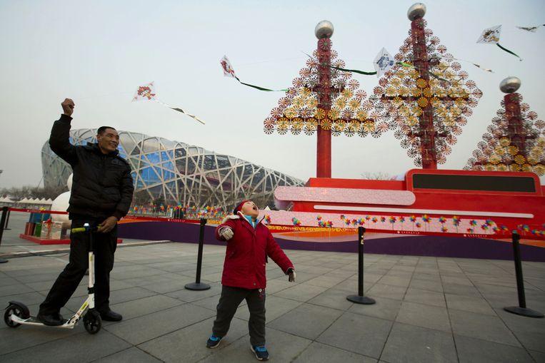 Kerstversieringen in Peking, met op de achtergrond het iconische olympische stadion 'het vogelnest'. Beeld ap