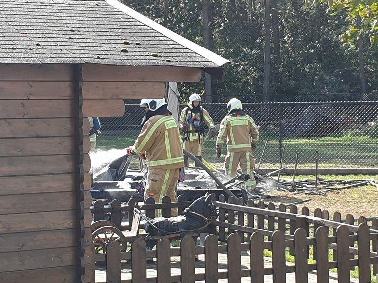 De brandweer tijdens de bluswerken aan de caravan.