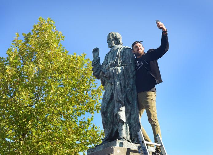 Rapper Dzenan Halilovic maakt een selfie met Jacob Cats, die hoog op z'n sokkel in Brouwershaven staat