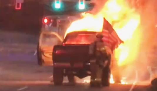 De patriottistische brandweerman haalt de smeltende vlag uit de vuurzee.