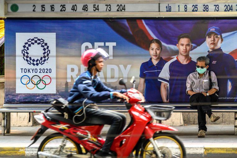 Een man met een mondkapje zit bij een bushalte voor een advertentie van de Olympische spelen van 2020 die in Tokio zullen plaatsvinden. Beeld AFP